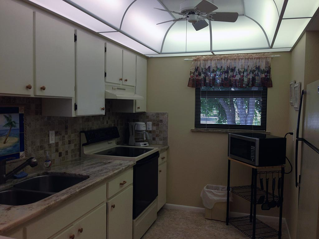 Florida condo kitchen includes stove, microwave oven, and coffee pot