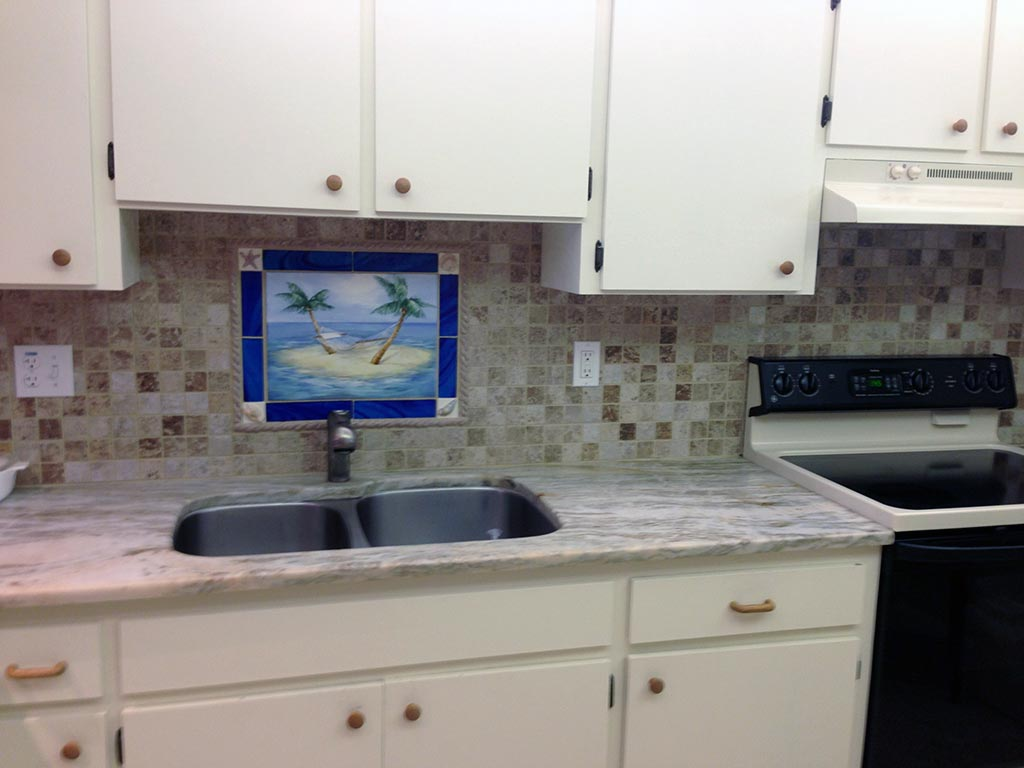 Florida condo kitchen sink with palm tree backsplash